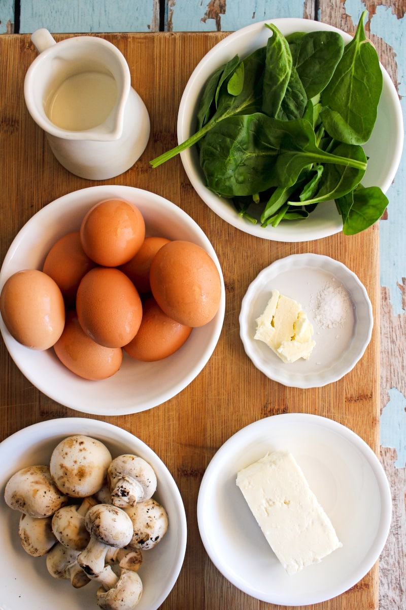 Top view of ingredients in white dishes arranged on a cutting board.