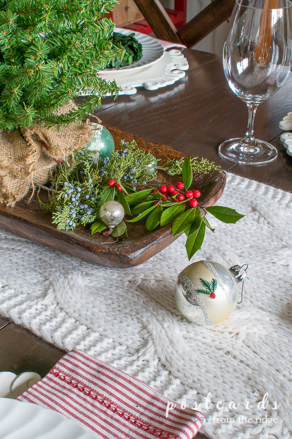 table with chunky knit table runner and vintage ornaments with cedar and holly branches