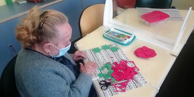Usuària d'Aviparc pintant i retallant una rosa