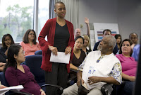 A woman stands to address a meeting