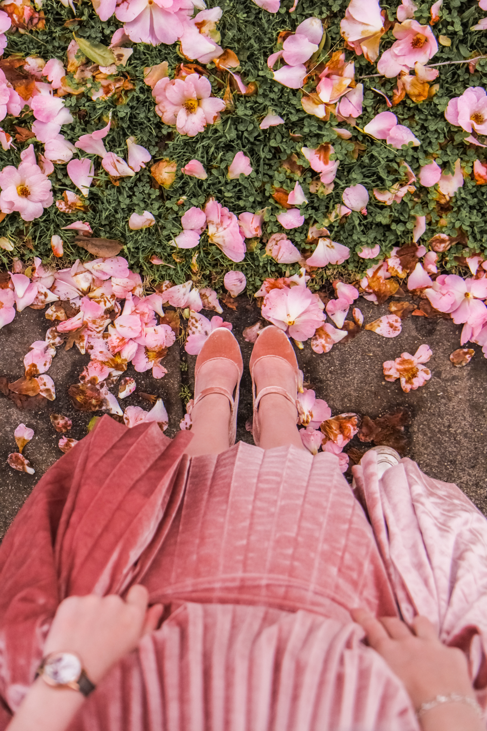 Liana looks down at her feet to take a photo of her pink velvet shoes in the camera. You're looking through the lens with her. Sophie's hands are in shot holding up the endless folds of soft pink velvet so you can see the shoes. She has an Olivia Burton watch and silver bracelet