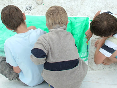 Back view of three young children kneeling on deck all painting a large piece of paper bright green
