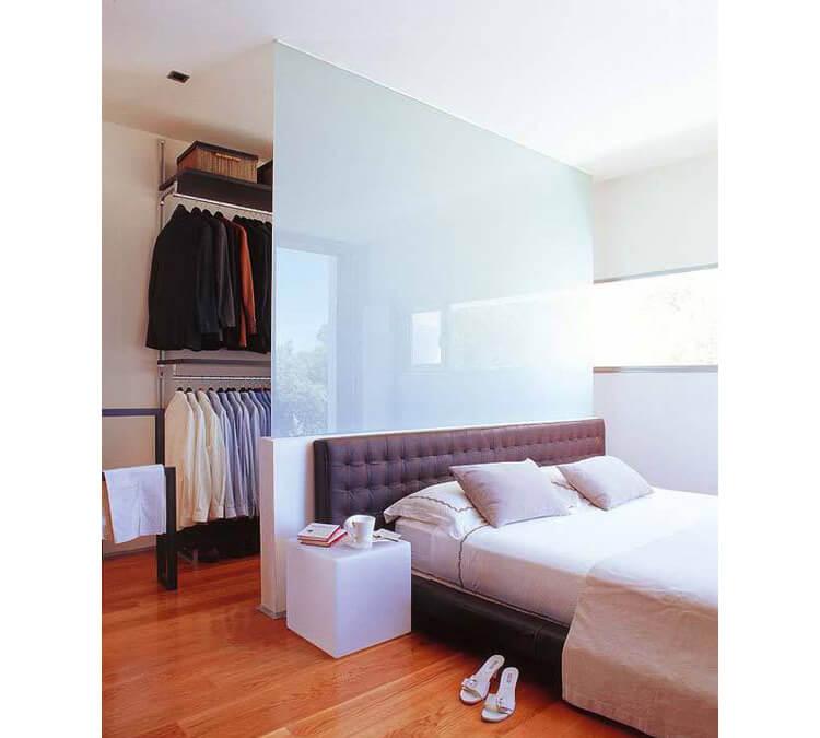 Esempio di cabina armadio in camera da letto con parete divisoria in vetro