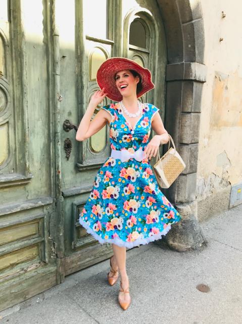 gudrun bluemel trägt das isabella dress summer blue von lady vintage und einen großen rosafärbigen hut