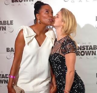 Picture of Emily Bett Rickards kissing Aisha Tyler