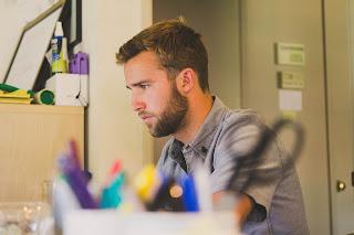 homem loiro com barba camisa xadrez trabalhando em seu escritório