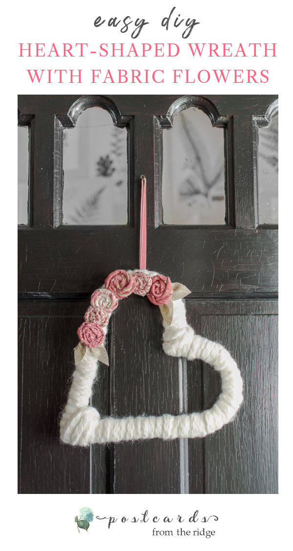 heart-shaped yarn wreath with fabric flowers on a black painted front door