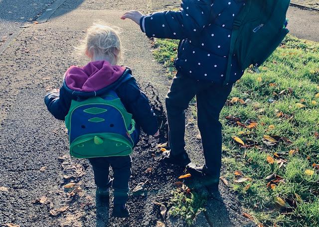 2 children in school uniform walking to school in no hurry on broken pavement in the winter