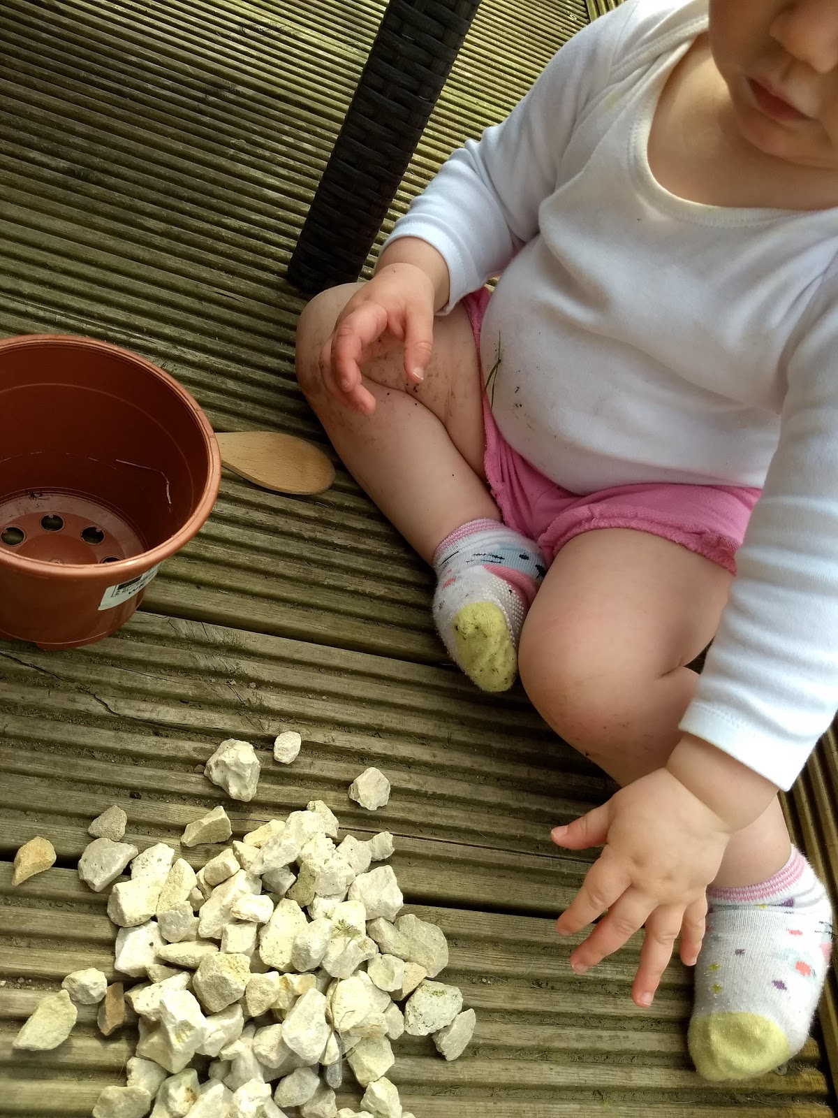 Toddler outdoor playing with pebbles.