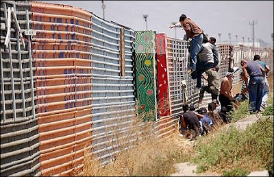 Illegal immigrants climbing over US border fence