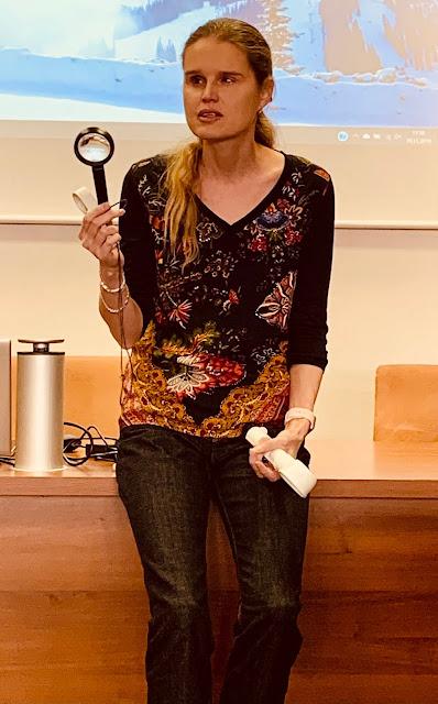 Linda drží v ruce lupu a přednáší posluchačům