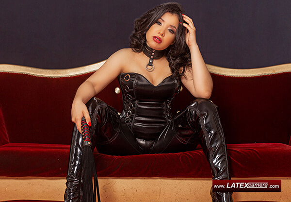 Latina Mistress on latexcamera in black leather corset and black PVC overknee boots