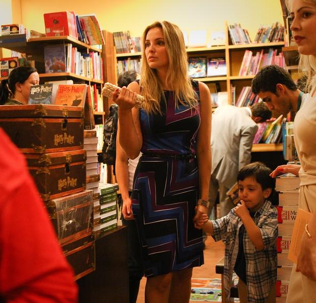 Marcela com vestido de estampas geométricas segura a mão do filho