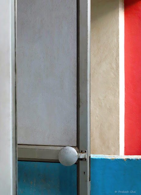 A Minimal Photo of an Open Aluminium Door with colorful walls in the background at Orbit Mall Jaipur.