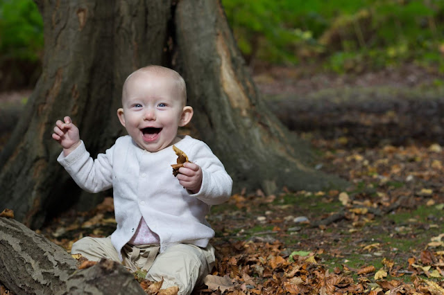 A laughing baby sitting in leaves in a forest perfect for Instagram