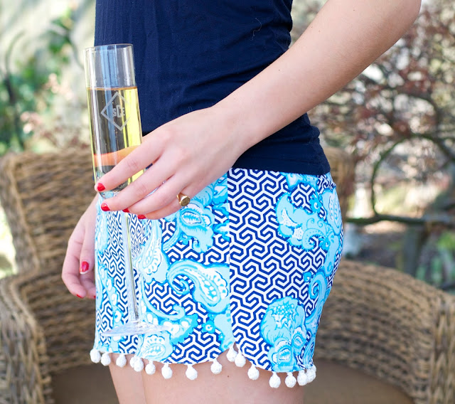monogrammed champagne flute and pom pom shorts