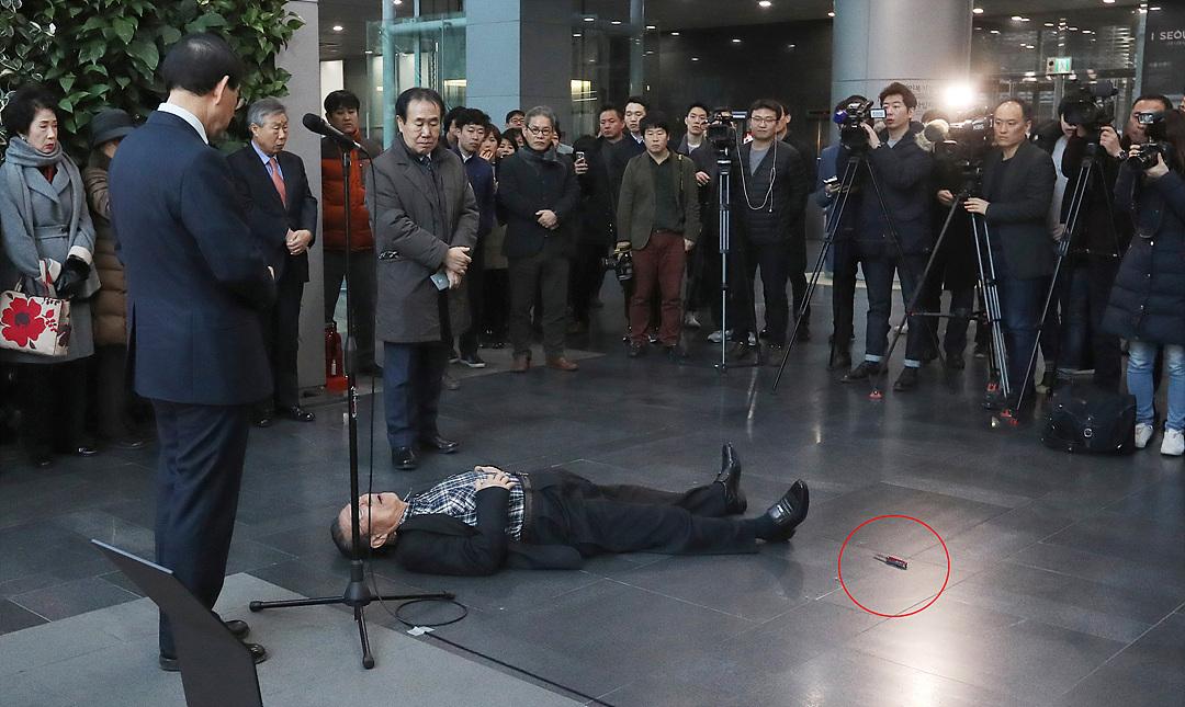 Coreano tumbado en el suelo tras rajarse el vientre con un cuchillo