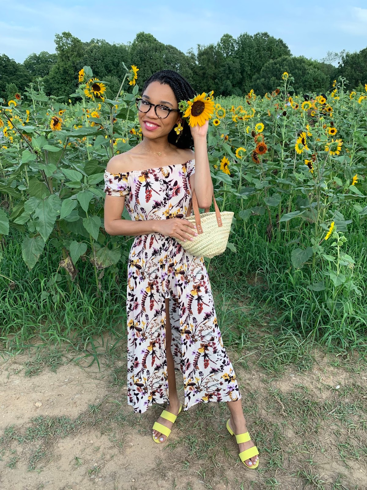 girl holding sunflower, sunflower photoshoot, sunflower field, flower jumpsuit, straw bag, summertime outfit, girl holding flower behind her head, box braids, crochet box braids