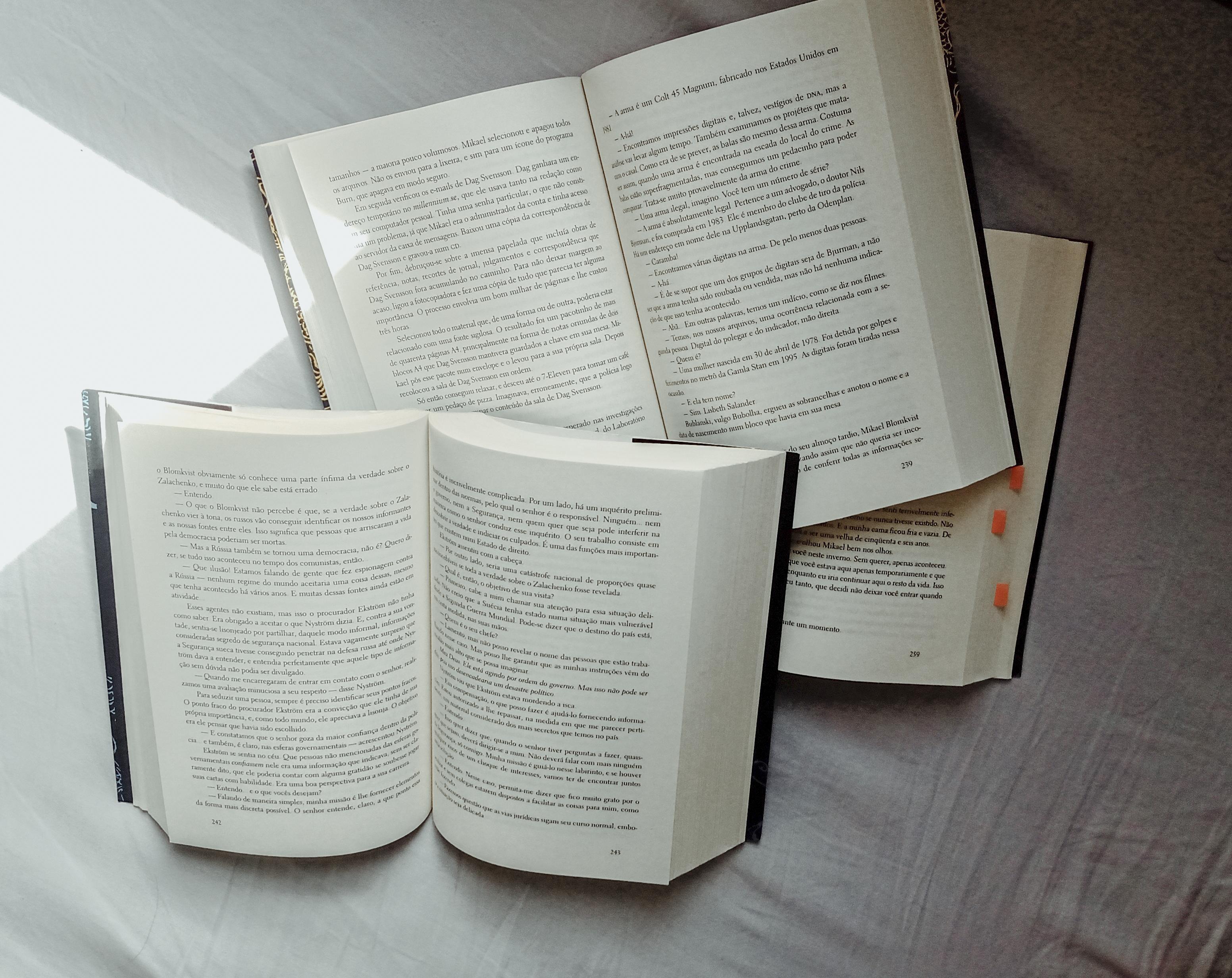 Três livros com as folhas abertas