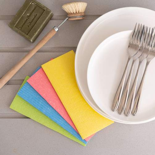 rainbow multi-color eco friendly and biodegradable sponges for cleaning the kitchen next to a white dish