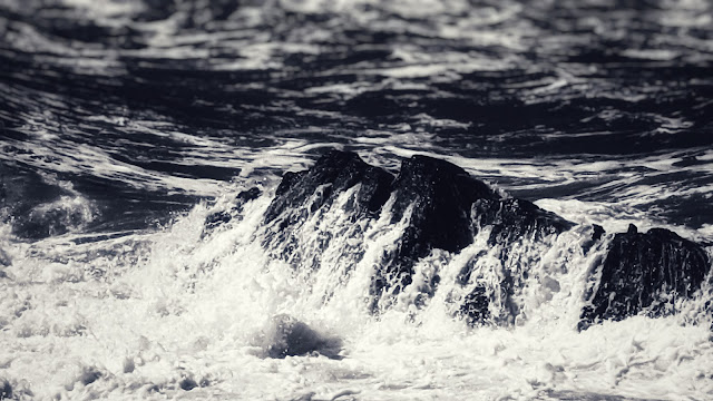 Wave crashing over a rock (black and white)