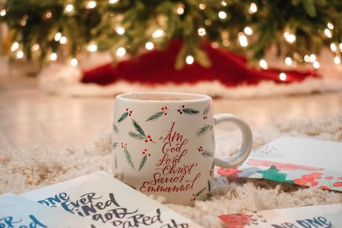 Names Of Jesus mug on floor in front of Christmas tree.