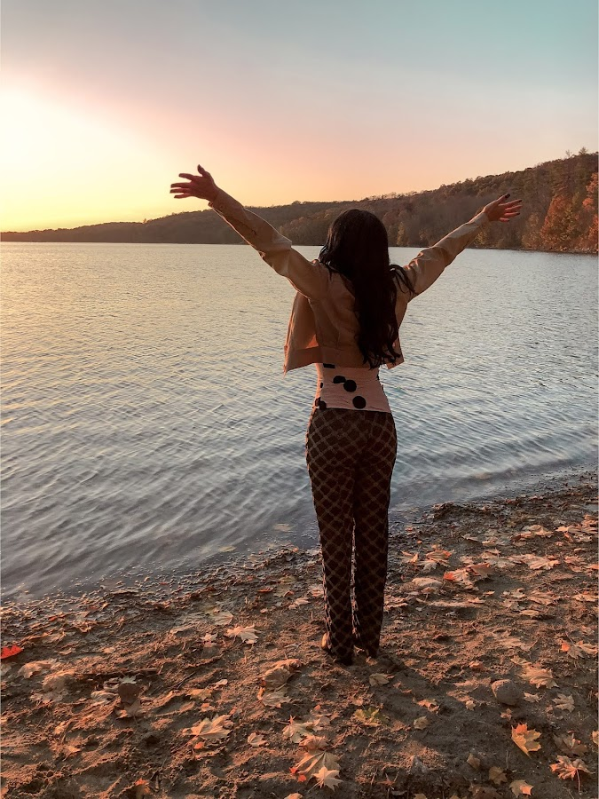 Arms open , high up, celebrating life, enjoying nature, Lina Mayorga Crop jacket sustainable, beige jacket, neutral tones, Versace logo pants, brown beige medusa logo, Jacquemus polka dot top strapple top, beige top with black dots, trees and leaves and a lake in the background, fall mood, North Salem, NY 2020