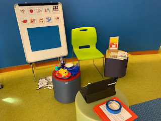 Looking at a chair next to a white board with visual activity schedule images and flannel board attachment. A cushion with small laptop is facing the chair and two smaller cushions with story time supplies are on either side of chair