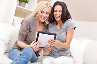 Photo of two smiling woman looking at a tablet