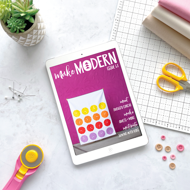iPad displaying front page of Make Modern magazine with Tiempo clock quilt on hot pink background, surrounded with sewing notions