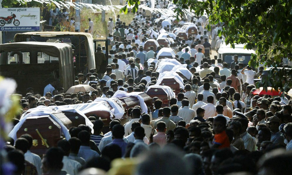 People carry coffins of their relatives for burial during a mass burial ceremony for victims of a landmine explosion by suspected Tiger rebels that killed at least 64 people, in Kabithigollewa village, about 210 kilometers (131 miles) north of Colombo, Sri Lanka, Friday, June 16, 2006.
