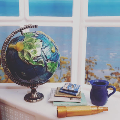 1/12 miniature scene of a windowsill overlooking the sea. On the windowsill is a metal globe, a stack of old books, a blue jug and an old telescope.