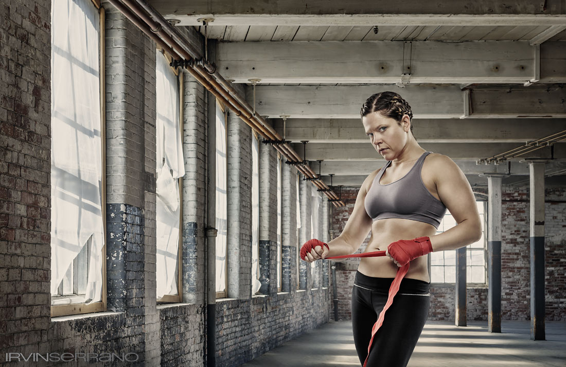 A woman UFC fighter stands in an empty, run down industrial space.