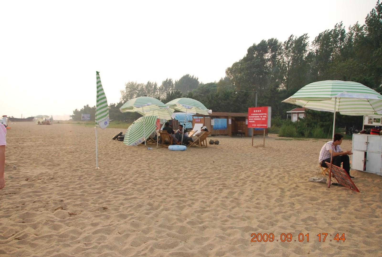 Strand mit grün-weiß gestreiften Sonnenschirmen