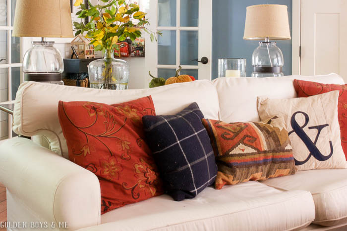 Fall decor in family room with white slipcovered sofa and plaid throw pillows - www.goldenboysandme.com