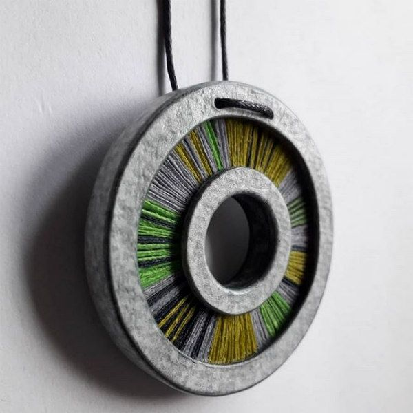 grey, green and gold circular paper pendant on black necklace cord