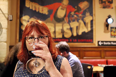 A redheaded woman drinking wine