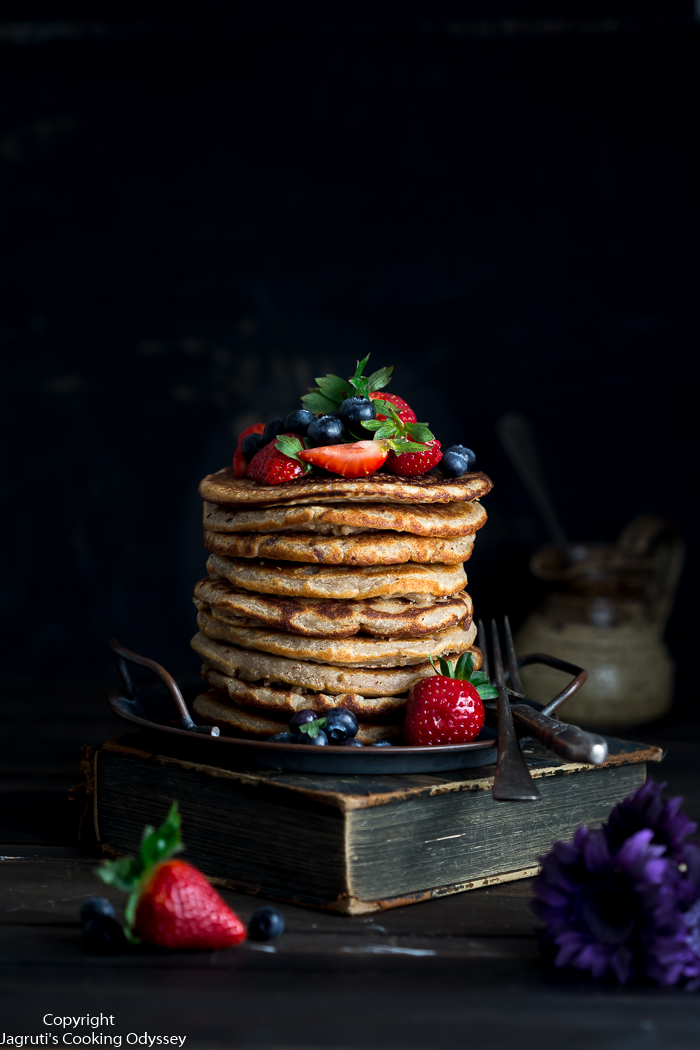 Image of a stack of pancakes with fruit as a topping