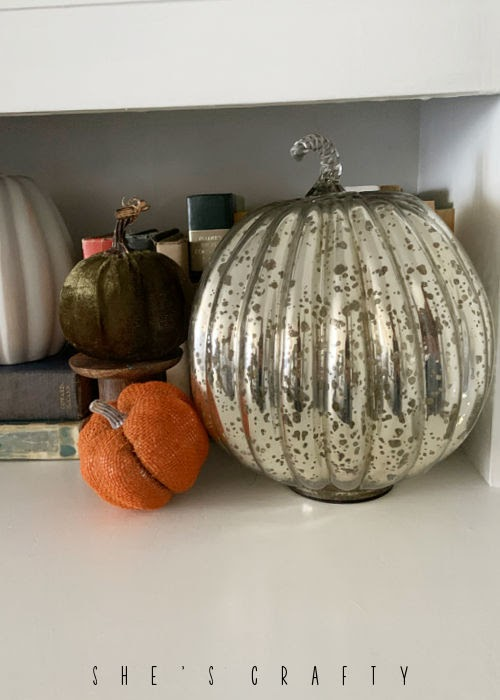 Mercury glass pumpkin on hutch with other pumpkin fall decor.