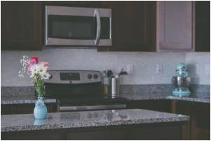 Kitchen with granite countertops and a flower vase on it