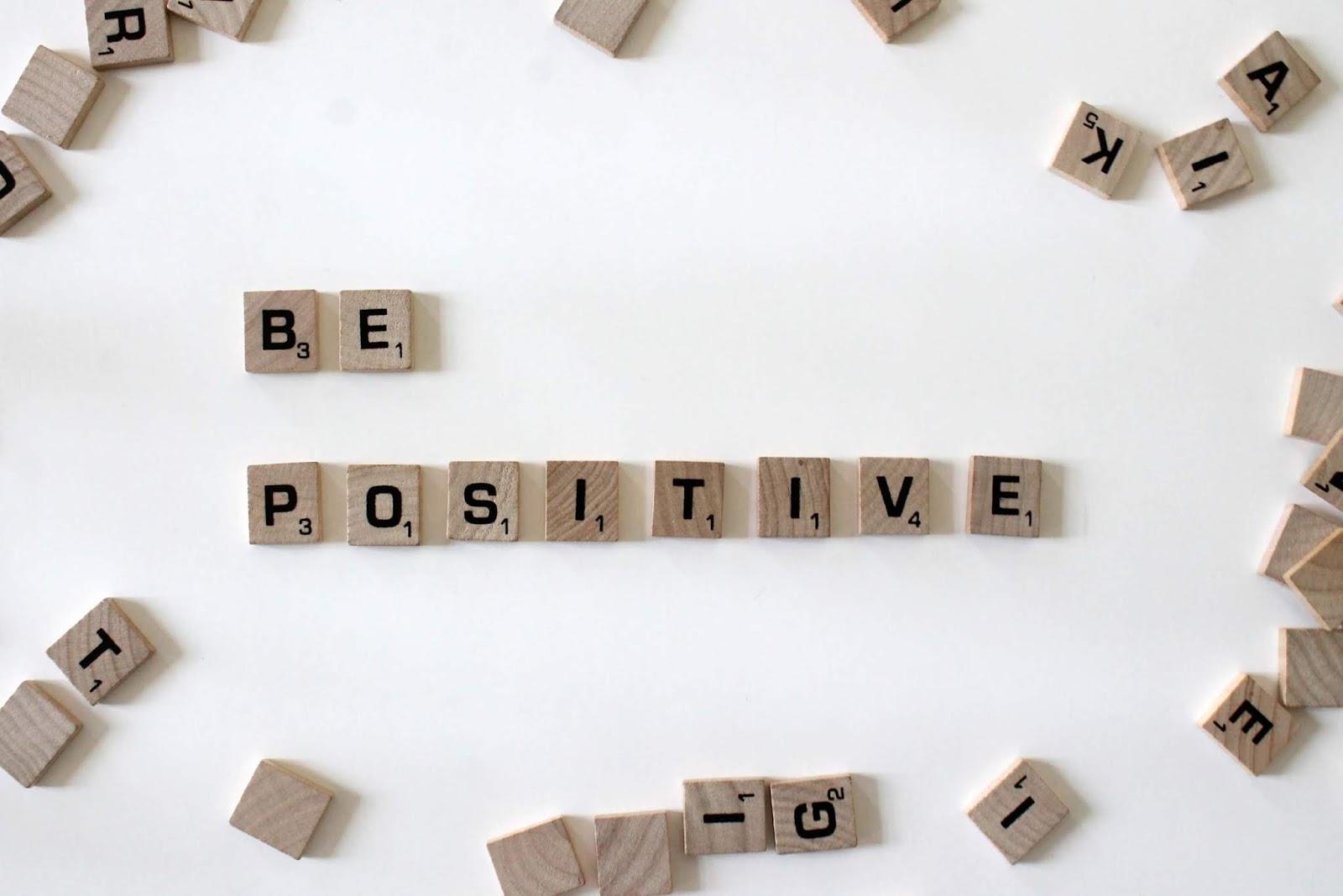 tasselli in legno che formano la scritta be positive