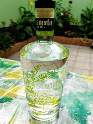 bottle of tequila on outdoor table with flowers in background