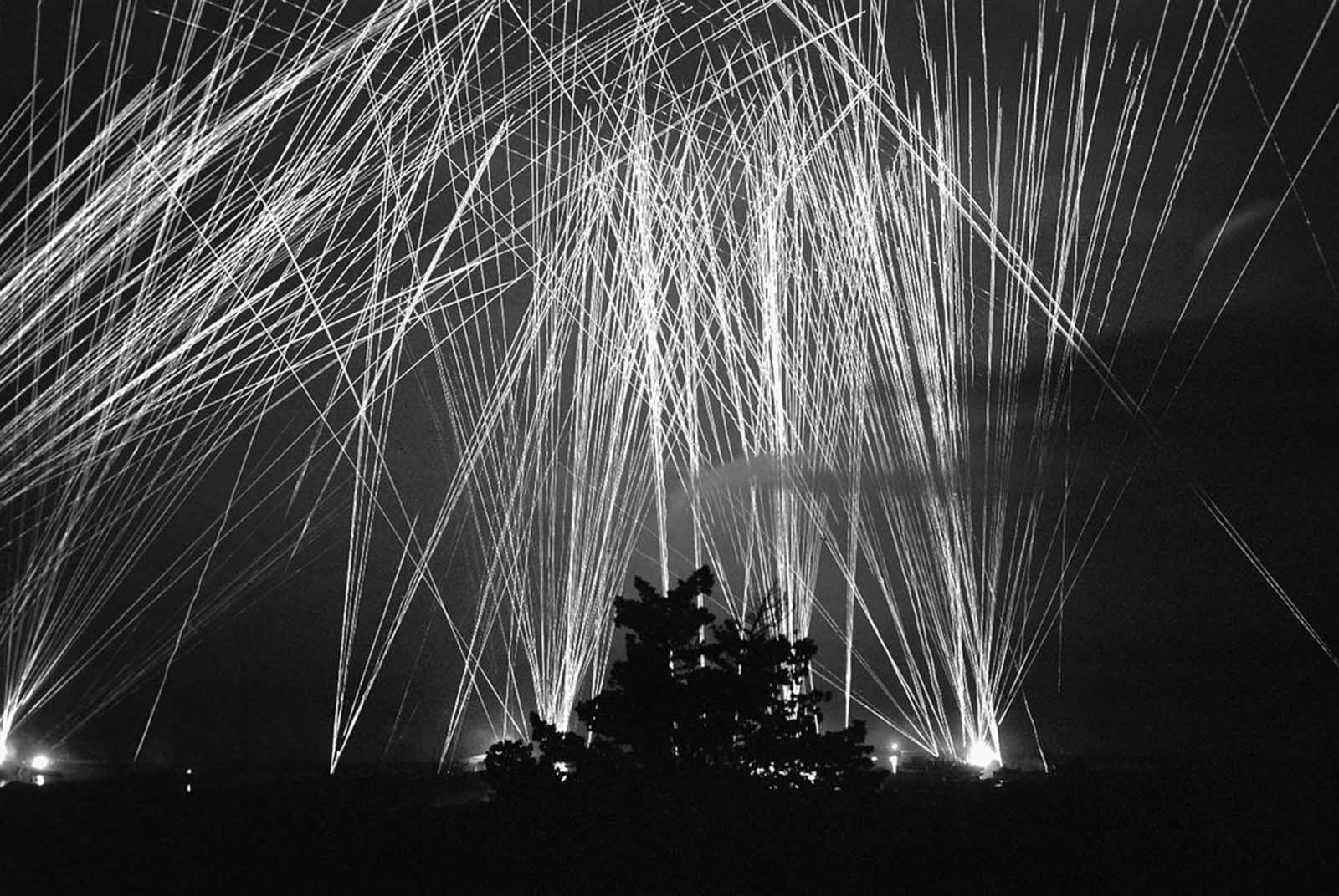 This pattern of anti-aircraft fire provides a protective screen over Algiers at night. The photo, recording several moments of gunfire, shows a defense thrown up during an axis raid upon Algiers in North Africa on April 13, 1943.