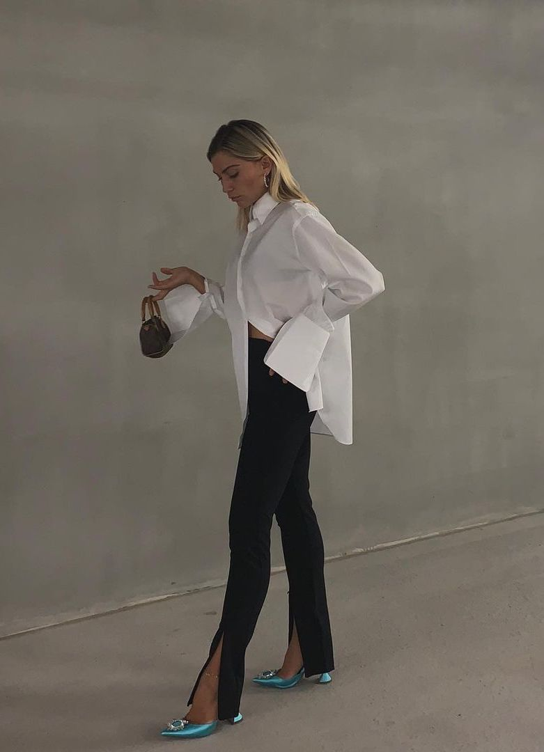 Modern summer wedding guest outfit idea ceremony style Natalia Georgala in a white button down shirt with wide cuffs, mini bag, black ankle slit pants, and green Amina Muaddi embellished heels