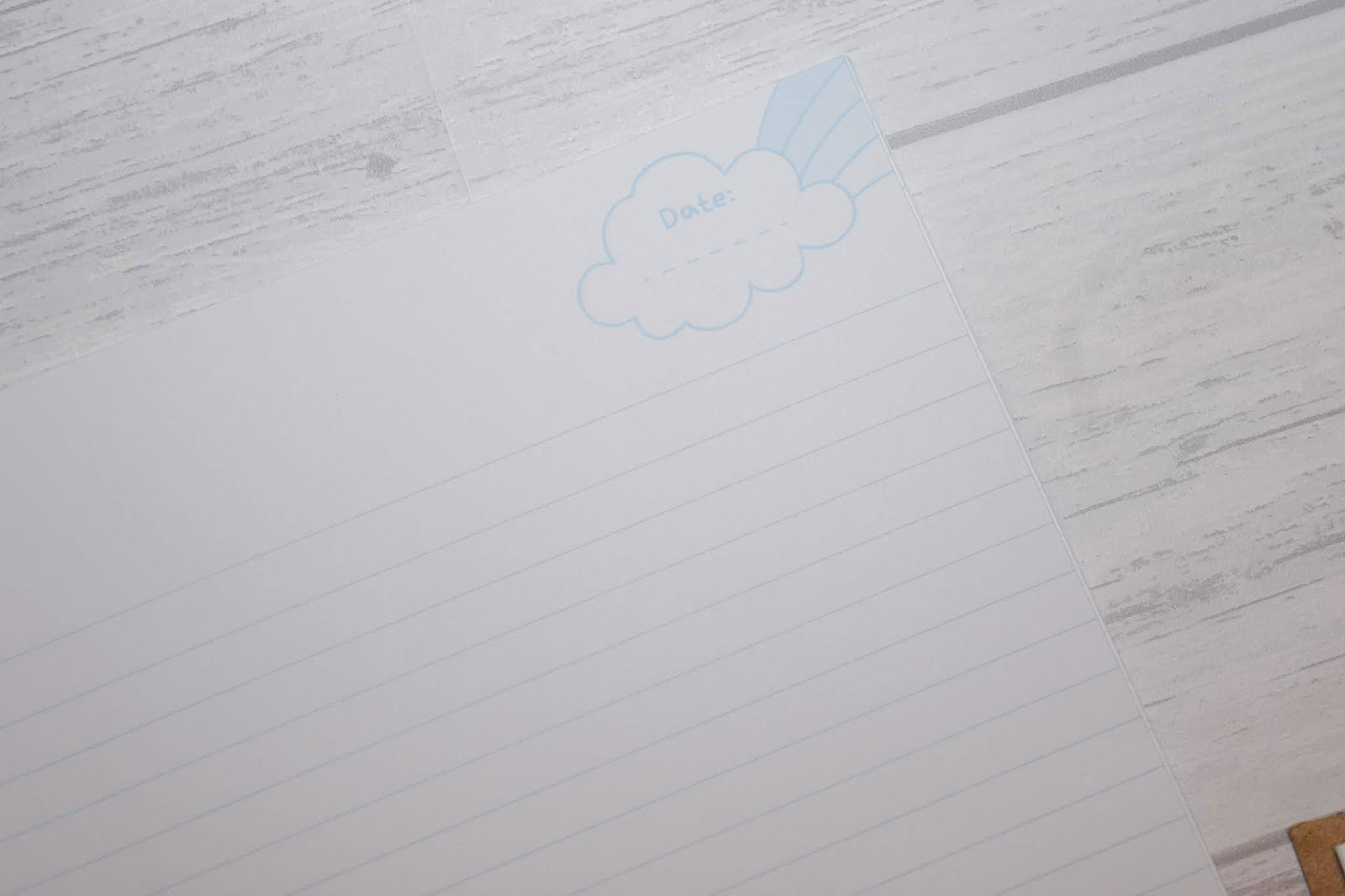 White paper with blue lines and a space to write the date in a cloud on the top right corner under the word date.