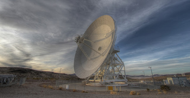 A Goldstone 111.5-foot (34-meter) beam-waveguide antenna tracks a spacecraft as it comes into view. The Goldstone Deep Space Communications Complex is located in the Mojave Desert in California. Engineers at NASA's Jet Propulsion Laboratory in Pasadena, California, will use antennas like this one to transmit a new set of commands to the Opportunity rover in an attempt to compel the 15-year-old Martian explorer to contact Earth.Image credit: NASA/JPL-Caltech