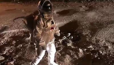 Pria berjalan bak di bulan