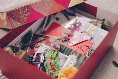 Pink shoebox containing cards, ribbons, watch, mementos