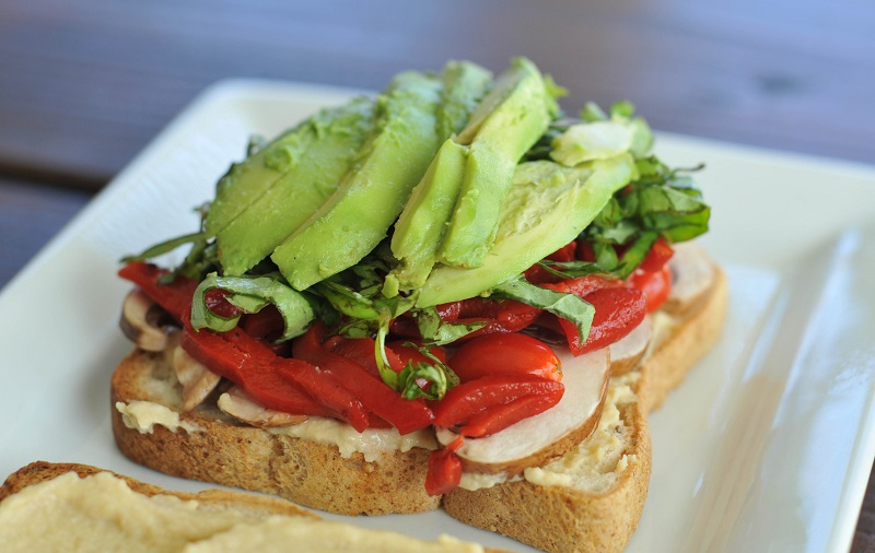 Gluten-free vegan sandwich with roasted red pepper, hummus, and avocado