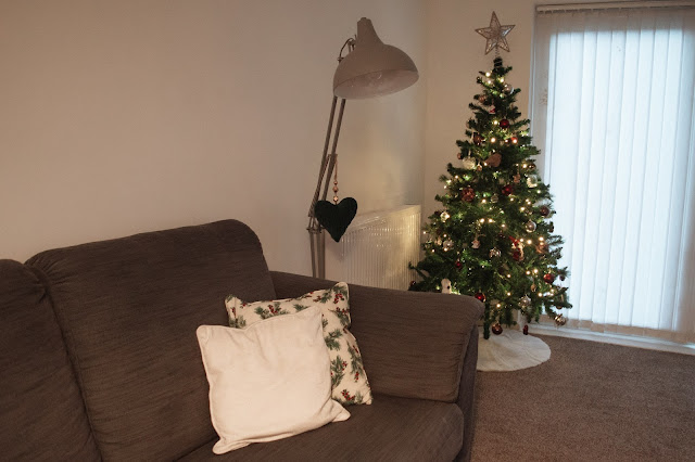 Christmas tree in a corner by a sofa with Christmas cushions